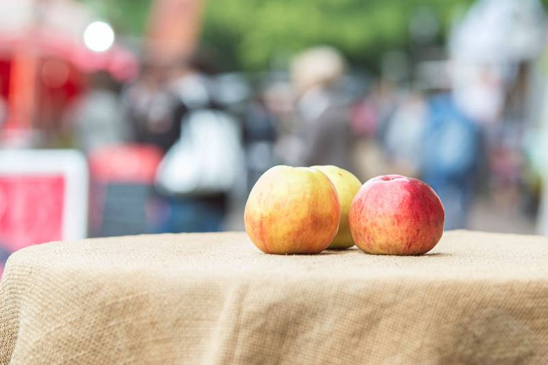 three apples sitting on table with festival in background