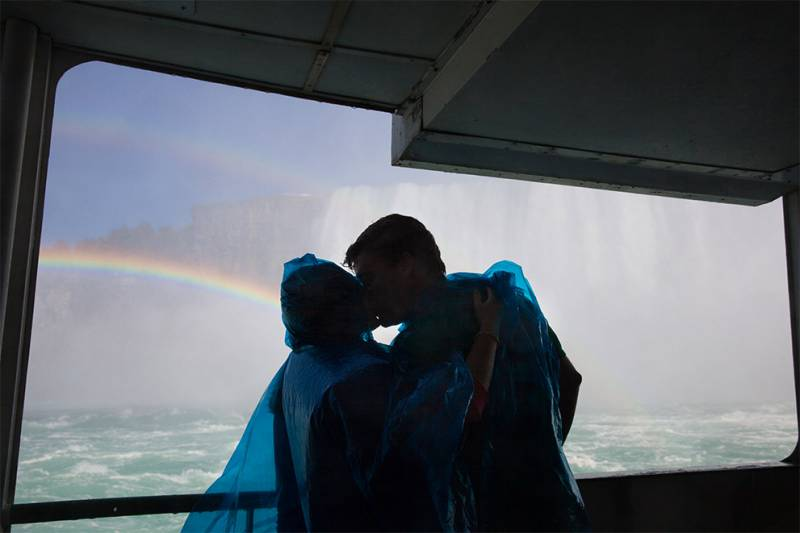 couple kissing on maid of the mist ferry boat with rainbow in background