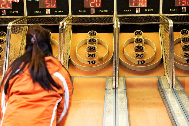 girl playing skee ball in at the falls arcade