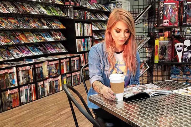 woman drinking coffee and reading comic book at comic book shop