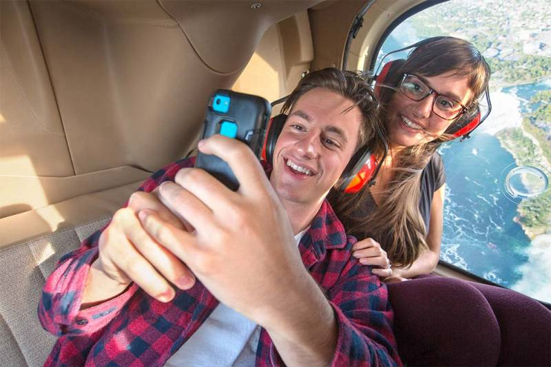 couple taking picture on helicopter tour attraction at niagara falls
