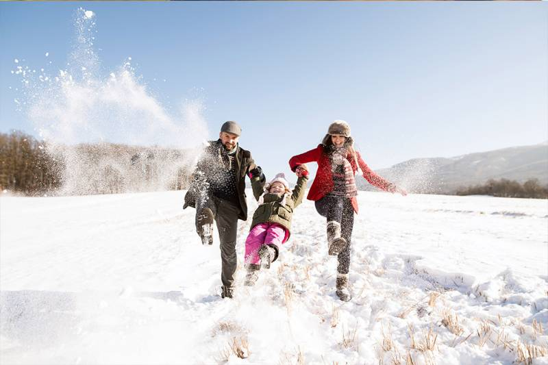 Family spending time together in winter kicking up snow.