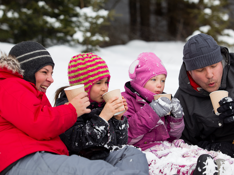 Family sitting in snow at Niagara Falls drinking hot chocolate.